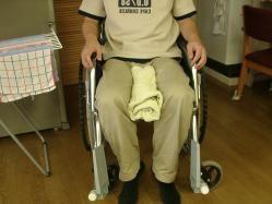 車椅子上、股の間にタオルを挟むイラスト