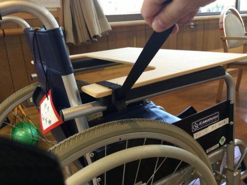 車椅子のアームレストに乗せ、万能ベルトで締め付ける。